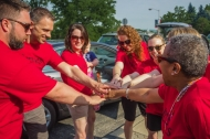 A team of University of Cincinnati faculty and staff, all in red T-shirts, come in a circle for a team break.