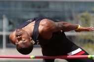 An African-American University of Cincinnati track athlete makes a dramatic backwards leap over the high bar