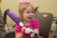 A little girl with a prosthetic hand holds a plastic baseball bat