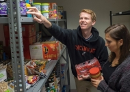 A young man with a woman reaches for an item on a top shelf of a food pantry.