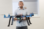 A man is blurry in the background of a photo of a working drone.