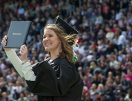 Graduating student holds up diploma in Nippert Stadium