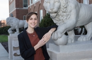 A University of Cincinnati student leaning on one of the university's mascots, a stone lion statue.