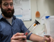 Researcher holds test tube of mosquitoes