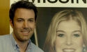 Movie promotional poster of Ben Affleck posing for a photo in front of a picture of his missing wife.