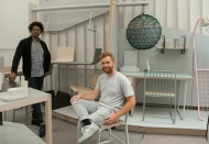 Two young men sit in an room created for a design competition