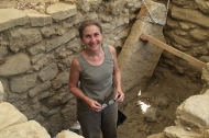 A woman, UC professor Sharon Stocker, stands deep under ground level in a tomb discovered in Greece.