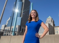 A pretty girl in a bright blue dress, Emily Bleuher, stands in front of the Cincinnati skyline.