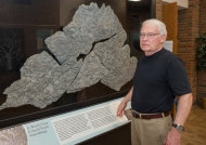 An old distinguished gentleman stands next to a display of fossils.