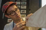 A young man in glasses and a plaid fabric cap works the grain of a fine piece of wood.