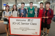 Chinese students hold up a welcoming banner to arriving students from China to the University of Cincinnati