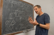 A professor stands next to an old-fashioned chalkboard that has physics and mathematical equations on it.