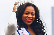 A beautiful black woman and University of Cincinnati graduate Ashley Nkadi in a crown and a beauty queen sash.