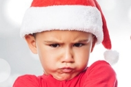 Pic of a kid in a Santa cap frowning.