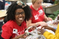 An African-American woman with a big, big smile looks at the camera while participating in UC Serves, a day of service for UC faculty and staff.