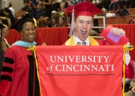 One UC graduate in a cap and gown holds a banner that says University of Cincinnati.