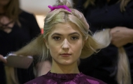 A pretty blonde model get hair extensions put in for the University of Cincinnati's fashion show.