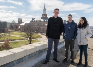 Three students stand on a roof with an overview of the University of Cincinnati behind them