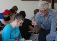 A University of Cincinnati professor, Ricardo Moena, with glasses at the end of his nose, leans in to a student in a classroom.