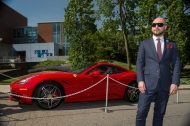 A slick bald man in sunglasses and an imported dark suit stands next to a red Ferrari sports car