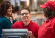 A woman with short cropped hair stands behind a cash register while two supervisors look on.