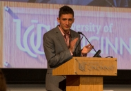 A young man in a suit stands at a University of Cincinnati podium