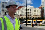 A man with a white construction helmet and flourescent traffic-control vest stands proudly with the new Cincinnati streetcar in the background.