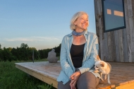 A blonde woman sits on the edge of a deck of her tiny house with her Chihuahua dog