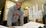 A young man with close-cropped hair and in a University of Cincinnati sweatshirt looks over blueprints while at his co-op job.