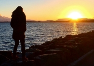 The bright yellow sun sets, just over the horizon, as a solitary figure walks across the rocky Iceland shore.