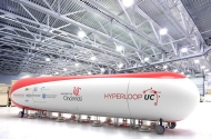 A strange white-and-red enormous tube vehicle sits in a warehouse.