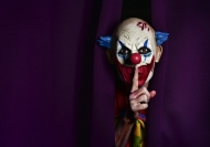 A creepy clown makes the gesture of finger to lips to Shhhhh