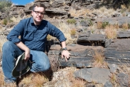 Man in glasses, blue jeans and blue shirt out along the ridge pointing to a fossil.