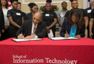 University of Cincinnati president Neville Pinto at a table signing an agreement with young students behind him.