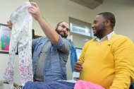 Two men look over a pair of slacks at the University of Cincinnati's LGBTQ's Closet of gently used clothing.