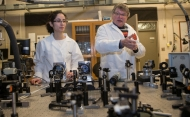 Two scientists in white lab coats behind lab equipment.