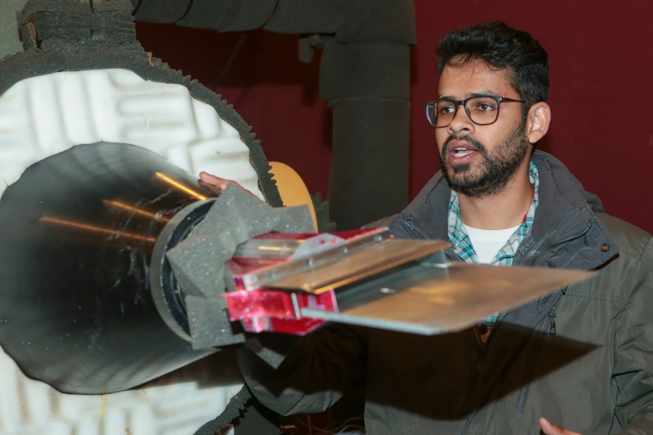 UC doctoral student Aatresh Karnam stands in front of a supersonic jet engine mounted to the floor in an anechoic chamber. UC researchers can affix nozzles of different shapes such as the long, rectangular one pictured. Karnam also attached an adjustable metal plate to the end to study changes in engine noise.