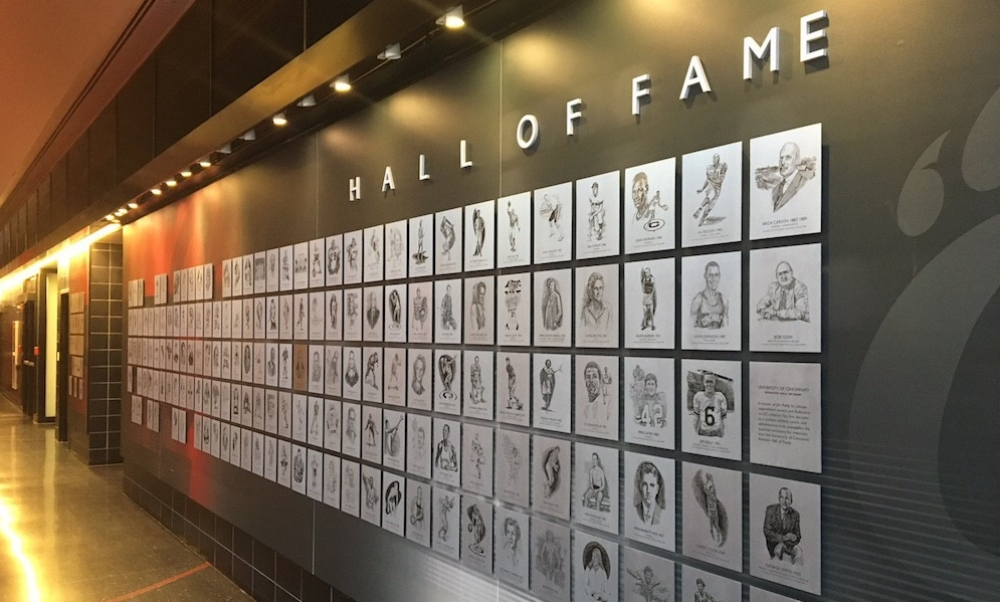 The James P. Kelly Athletics Hall of Fame wall displaying portraits of each of the honorees at the University of Cincinnati.