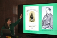 Professor points to slide of Irish sheet music covers at a presentation.