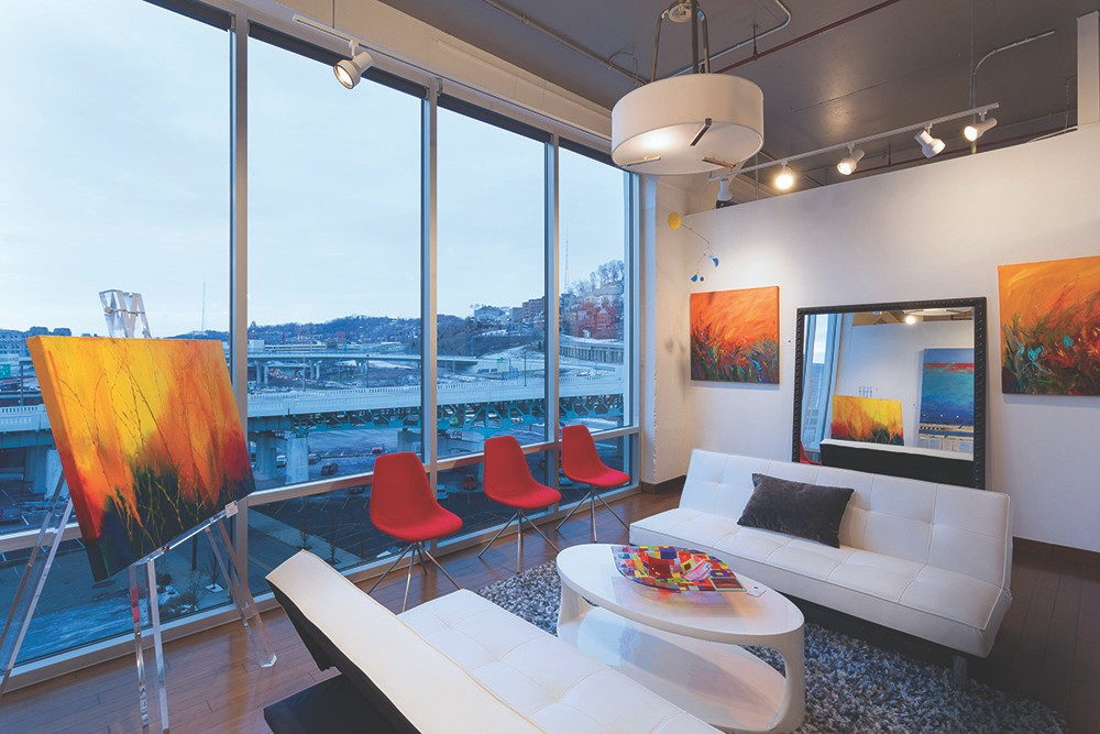 White couches, red chairs, orange-red paintings and floor-to-ceiling windows fill this area of Art Design Consultants.
