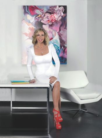 Litsa Spanos sits on a table in the ADC space: a blonde woman in a white dress, white table, white chair, white walls with a painting of a woman in the background.