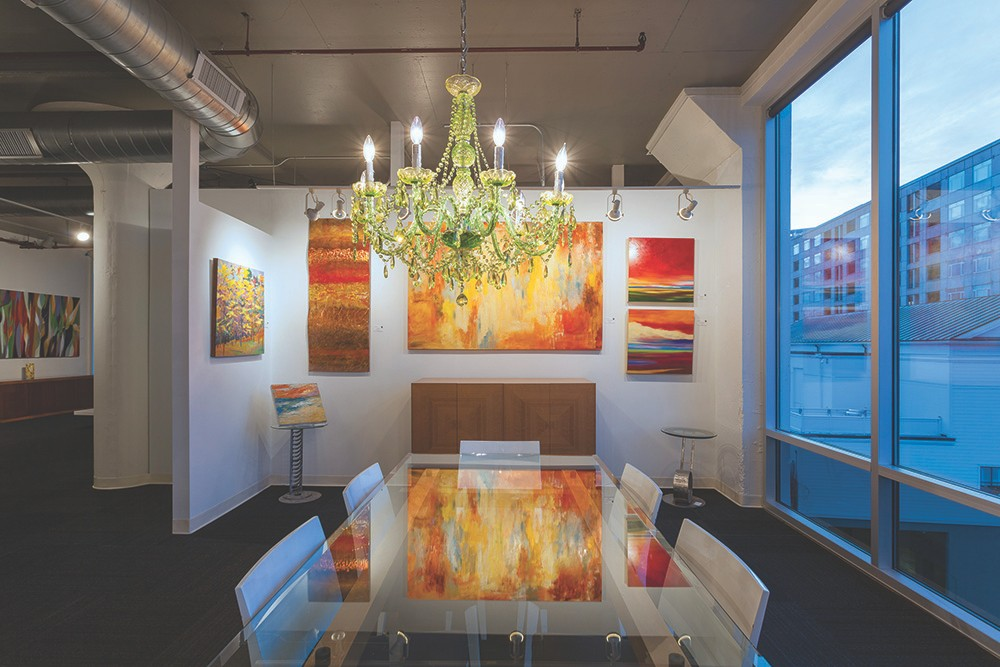 A chandelier, orange-red paintings and glass table fill this area of Art Design Consultants.
