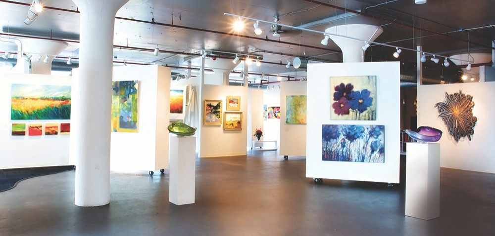 The Art Design Consultants space, a renovated warehouse is full of vibrant artwork — paintings and glass sculptures against white walls. Photo/provided