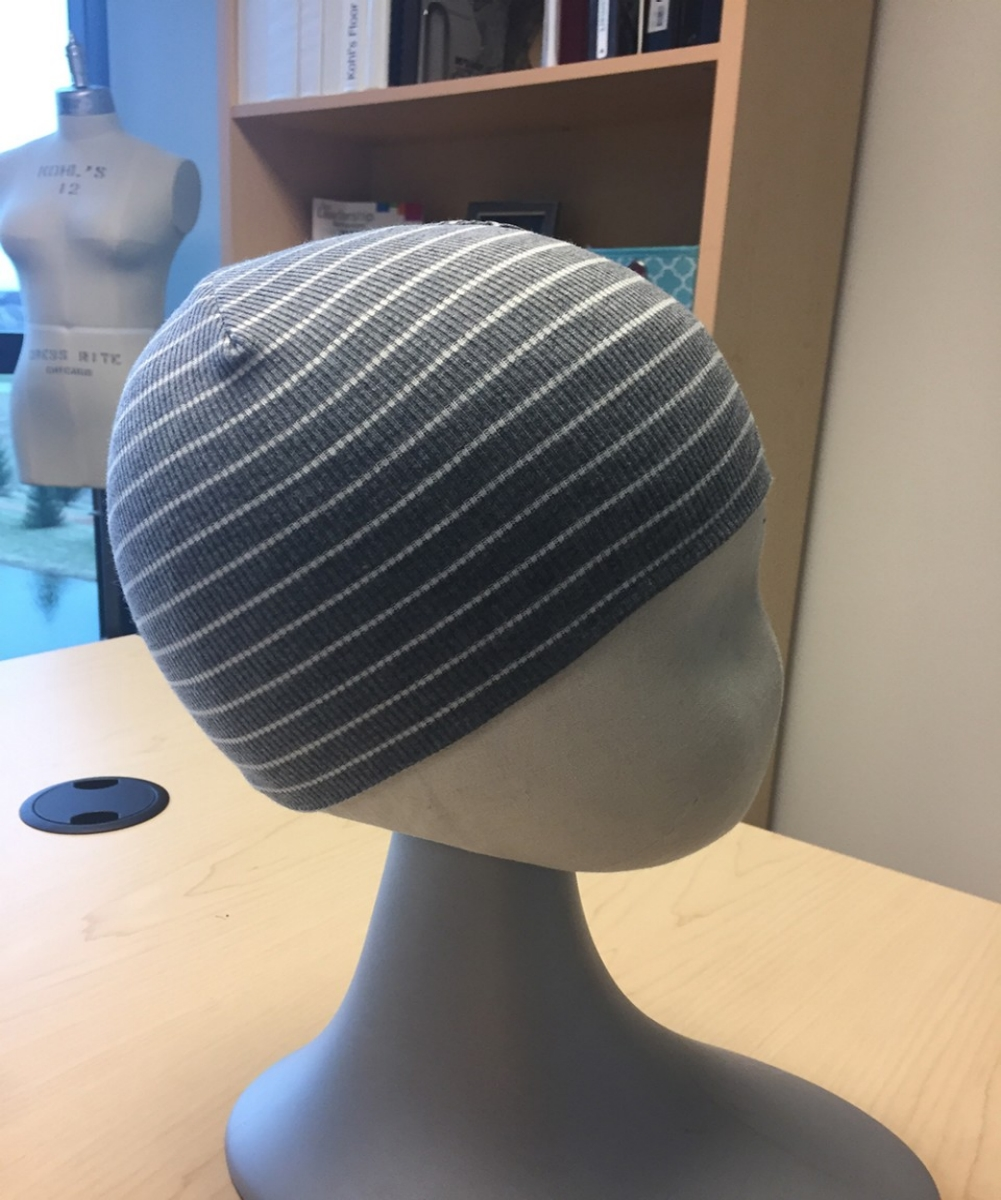 A striped knit cap is being fit on a mannequin head.