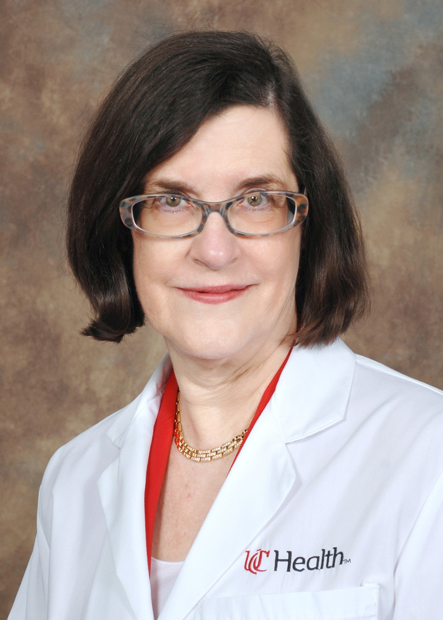 Dr. Elyse Lower poses for a headshot with glasses and a white UC Health lab coat.