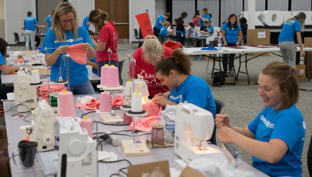Volunteers sew pink hats in a large room of volunteers creating care-package items for cancer patients.