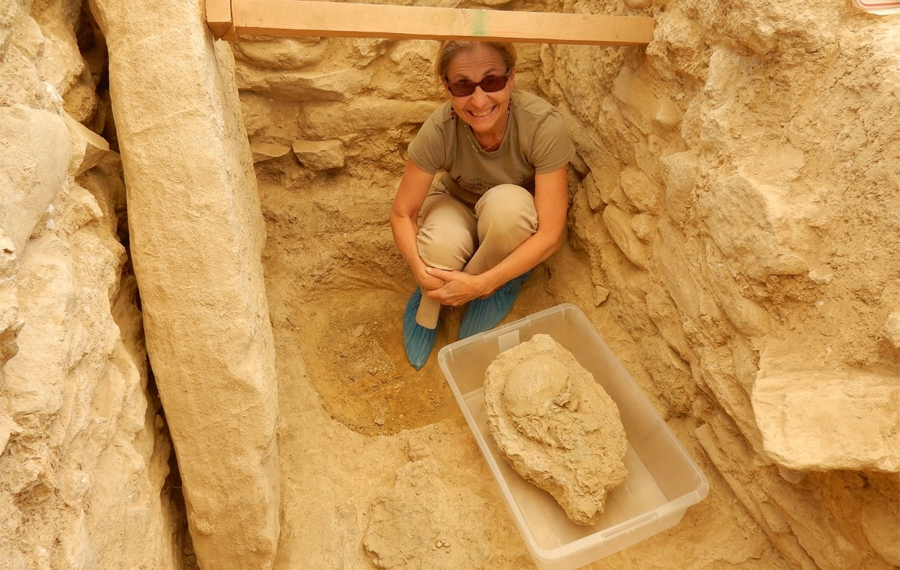 Shari Stocker, a senior research associate at the University of Cincinnati, poses with the remains of a Greek warrior unearthed in southwest Greece.