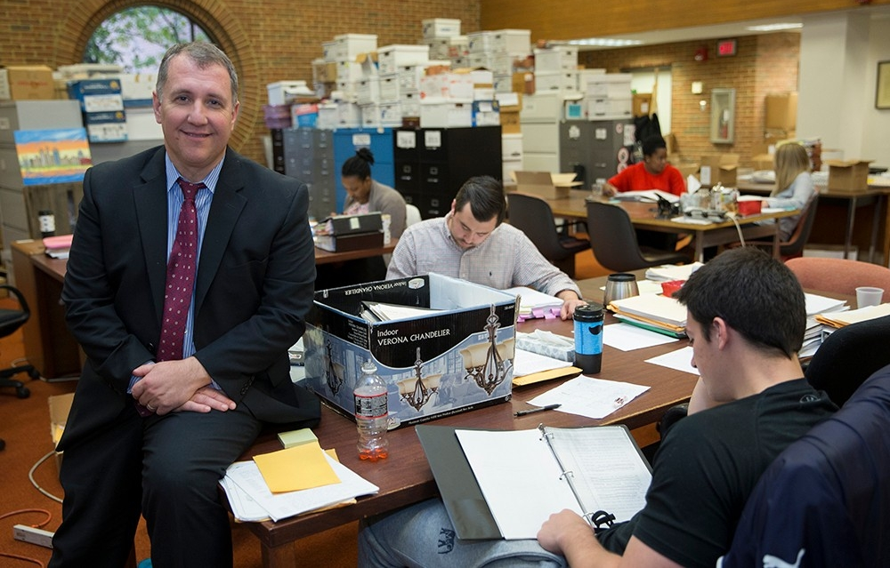 Mark Godsey sits on a desk in a room with students