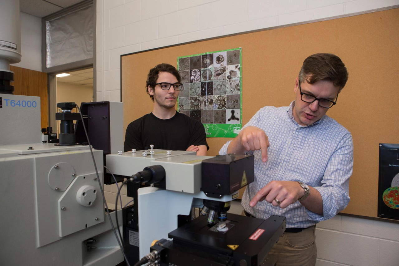 UC geology professor Andrew Czaja, right, and graduate student Andrew Gangidine use a spectroscopy machine in Czaja's lab.