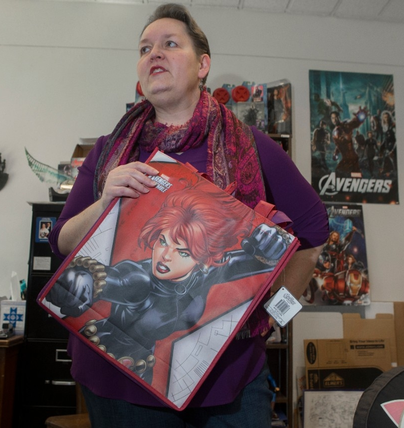 UC pop culture expert Rebecca Borah holds up a Black Widow tote bag in her office in McMicken Hall. Borah said Black Widow is the most controversial character in the Marvel Cinematic Universe.